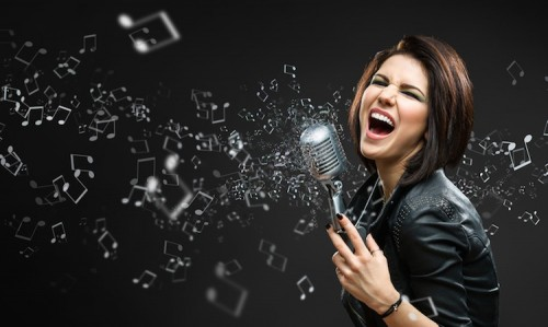 Half-length portrait of female singing rock musician keeping mike on grey background